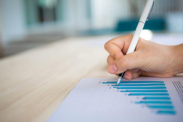 Mano con un bolígrafo escribiendo en un papel con un gráfico de barras Foto gratis