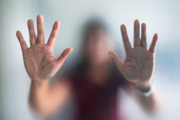 Mano borrosa de la mujer detrás del pánico de vidrio esmerilado, pánico y negativo oscuro emocional Foto Premium
