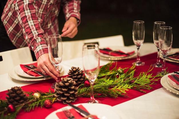 Mano colocando copa de champagne en mesa navideña