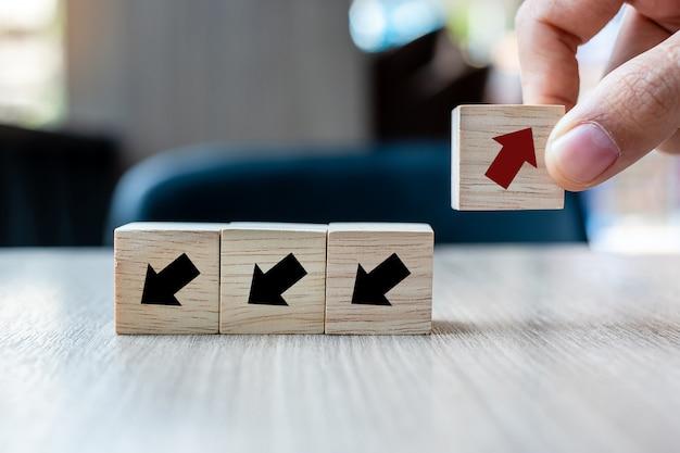 Mano colocando flecha roja bloque de madera Foto Premium
