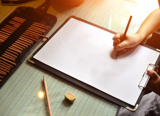 Mano con un lápiz escribiendo en una hoja en blanco   Descargar ...