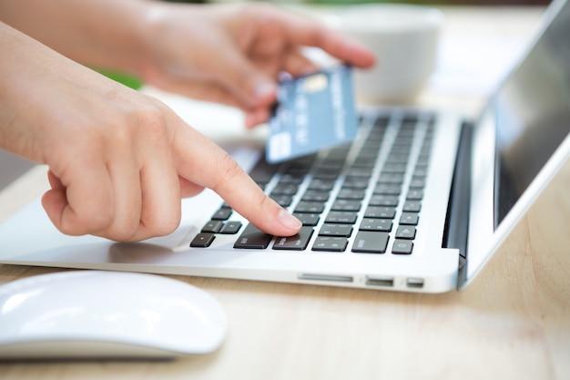 Mano con una tarjeta de crédito y un portátil Foto Gratis