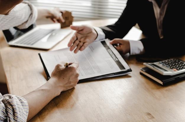Mano del contrato de firma del cliente del hombre joven para comprar casa con el agente inmobiliario Foto Premium