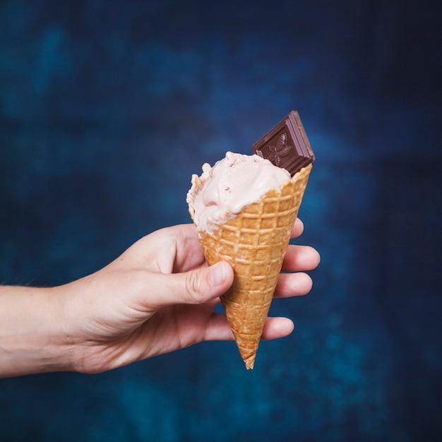 Mano de cultivo sosteniendo el cono con helado Foto gratis
