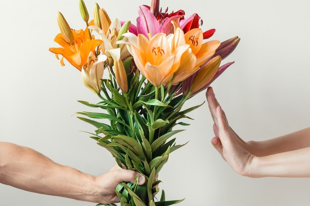 La mano le da un ramo de flores de lirios a una niña, la mujer se niega y muestra una señal de alto. Foto Premium