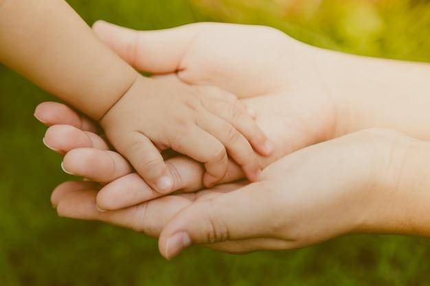 Mano de adulto agarrando mano de un bebé | Descargar Fotos gratis