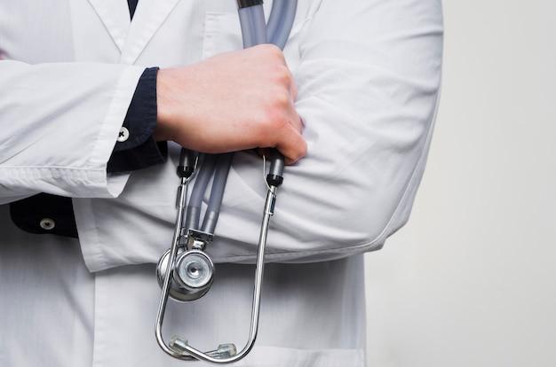La mano de un doctor de sexo masculino que sostiene el estetoscopio disponible contra el contexto blanco Foto gratis