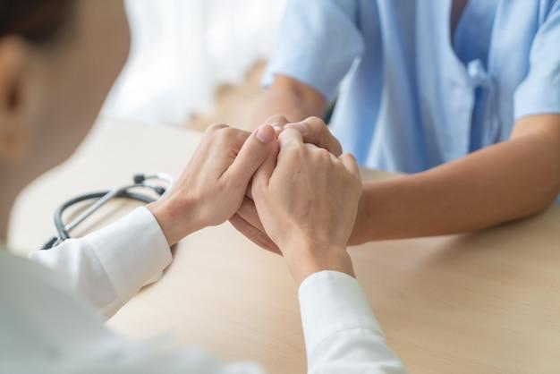 Mano de doctora sosteniendo a su paciente senior Foto Premium