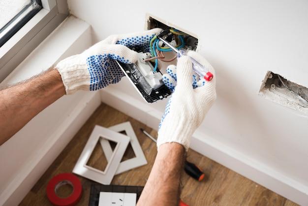 Mano de electricista instalando toma de corriente en casa. Foto Premium