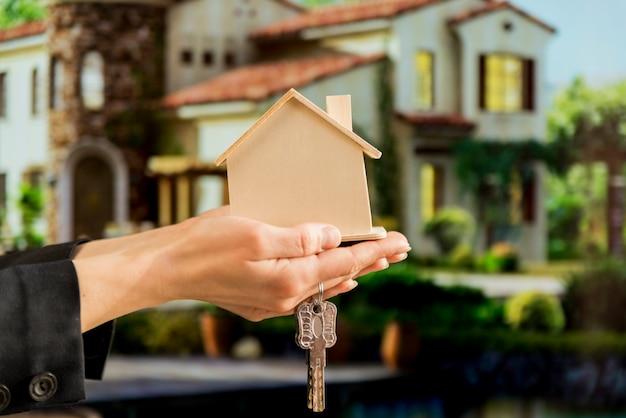 La mano de la empresaria que sostiene el modelo y las llaves de madera de la casa contra casa de la falta de definición Foto gratis