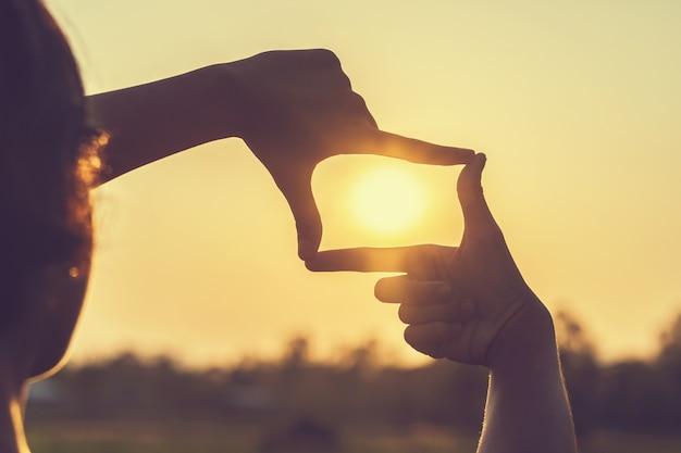 Mano encuadre vista distante sobre puesta de sol Foto Premium