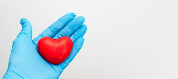 Una mano enguantada sostiene un corazón rojo. concepto de atención médica. copia espacio Foto Premium
