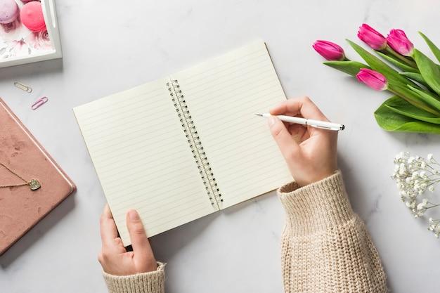 Mano escribiendo en cuaderno en blanco Foto Premium