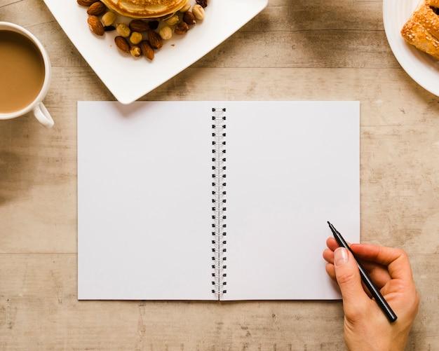 Mano escribiendo en cuaderno con café Foto gratis