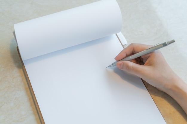 Mano escribiendo en una libreta Foto gratis