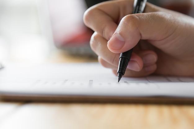 Mano escribiendo en un papel con un bolígrafo Foto gratis