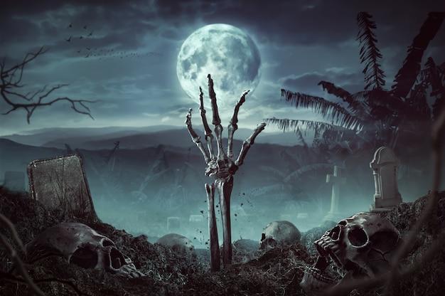 Mano de esqueleto zombie en la oscuridad de la noche de halloween. Foto Premium