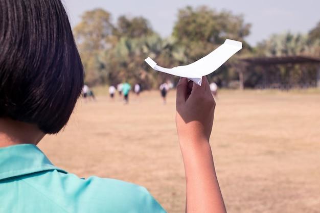Mano del estudiante que sostiene el aeroplano de papel en clase de la educación del tronco. Foto Premium