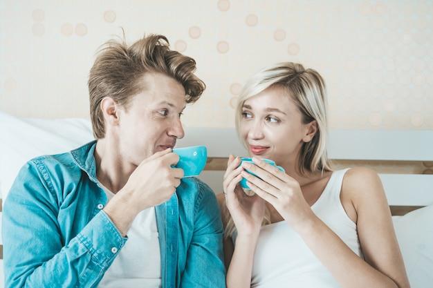 Mano feliz de los pares que sostiene la taza y que bebe el café por la mañana Foto gratis
