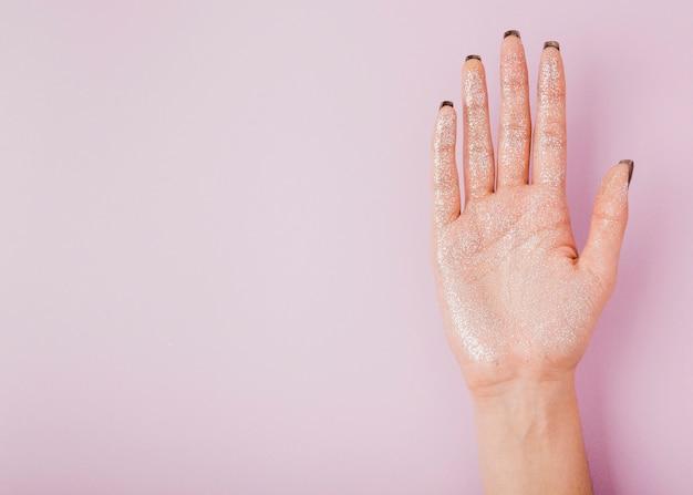 Mano femenina con brillo y copia espacio fondo rosa Foto gratis