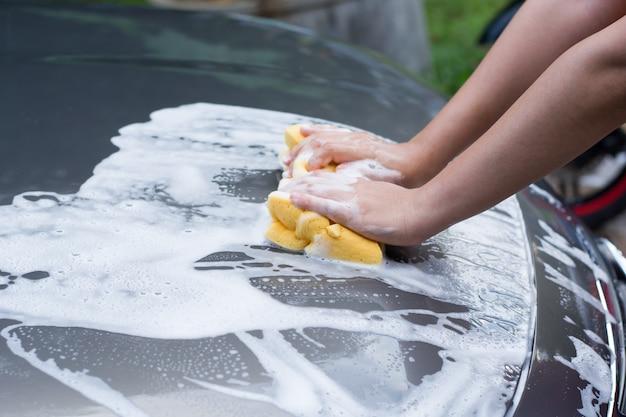 Mano femenina con coche de lavado de esponja amarilla Foto Premium