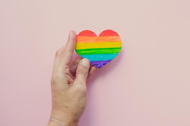 Mano femenina con corazón decorativo con rayas de arco iris Foto Premium