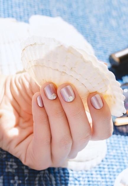 Mano femenina con diseño de uñas de color púrpura claro con decoración de conchas marinas. Foto Premium