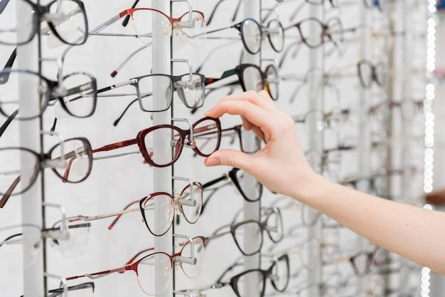 Mano femenina elegir anteojos en tienda de óptica Foto Premium