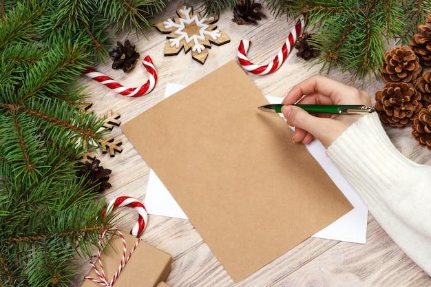 Mano femenina escribiendo una carta de navidad Foto Premium