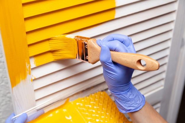 Mano femenina en guante de goma con pincel pintando puerta de madera con pintura amarilla Foto Premium