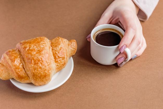 Mano femenina con manicura sosteniendo la taza de café y comer croissant. desayuno en estilo francés. Foto Premium