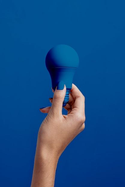 Mano femenina que sostiene la bombilla de azul clásico Foto gratis