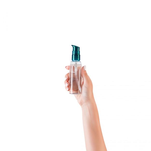 Mano femenina que sostiene la botella de crema de loción Foto Premium