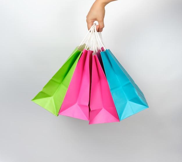 Mano femenina que sostiene cuatro bolsas de embalaje de compras de papel de colores Foto Premium