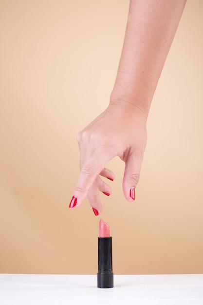 Mano femenina con uñas rojas tomando lápiz labial Foto gratis