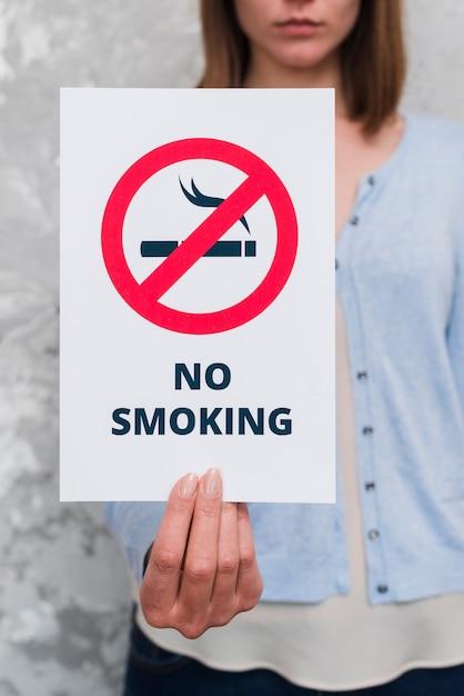 Mano femenina sosteniendo papel sin masaje de fumar Foto gratis