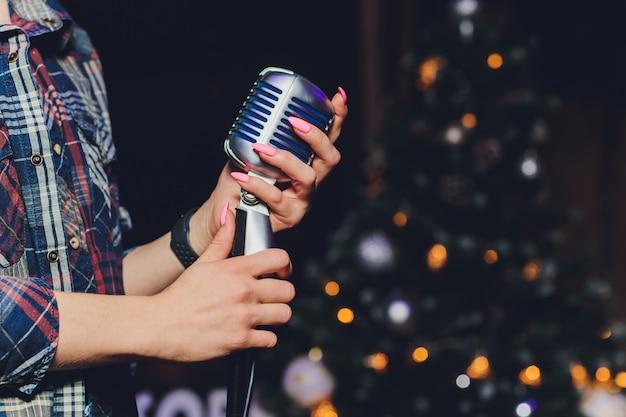 Mano femenina sosteniendo un solo micrófono retro Foto Premium