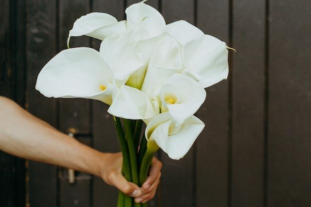 Mano Con Flores De Lirios De Cala En Una Madera Oscura