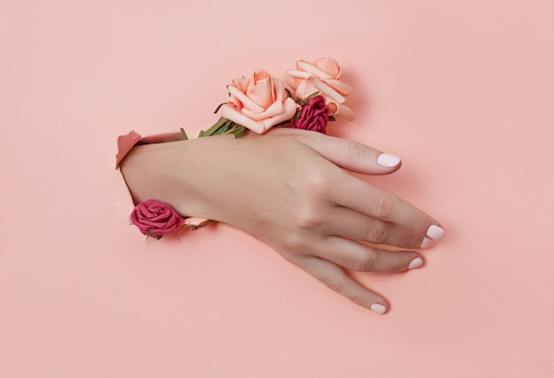 La mano con flores de papel y uñas pintadas se empuja a través de un agujero en el fondo de papel Foto Premium