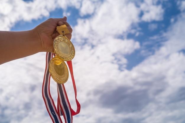 Mano ganadora levantada sosteniendo dos medallas de oro con cinta tailandesa contra el cielo azul. Foto Premium