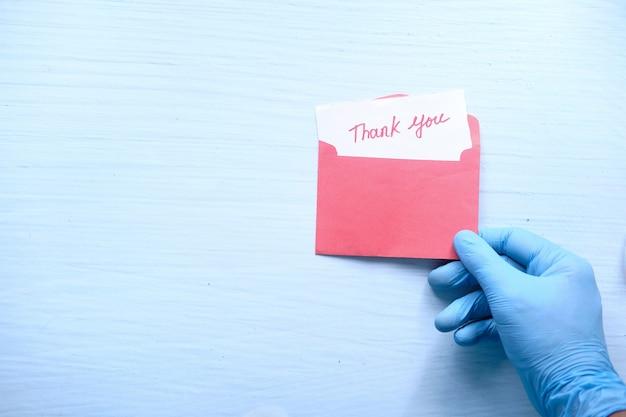 Mano en guantes protectores sosteniendo una carta de agradecimiento. Foto Premium