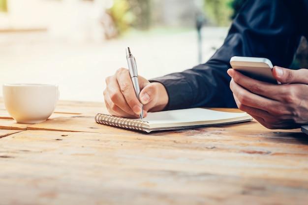 Mano del hombre de asia que escribe el papel del cuaderno y que usa el teléfono en la tabla de madera en cafetería con el filtro tonificado de la vendimia. Foto Premium