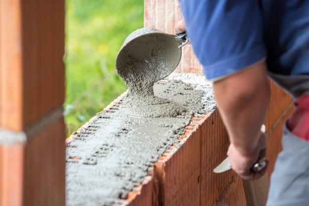 Mano de hombre construyendo muro de ladrillos Foto Premium