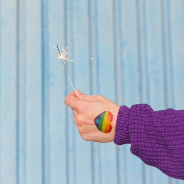 Mano del hombre con corazón de arco iris con bengala Foto gratis