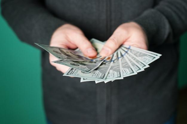 Mano del hombre dando billetes de 100 dólares Foto Premium