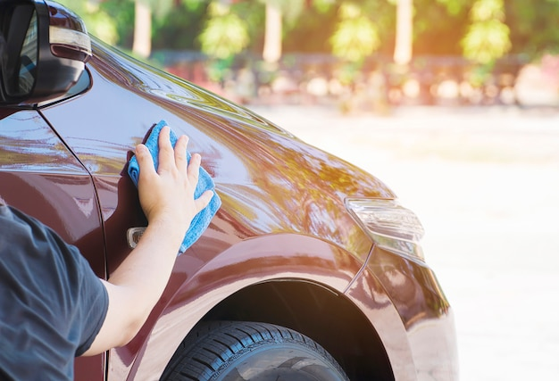 La mano del hombre es limpiar y encerar el coche. Foto gratis