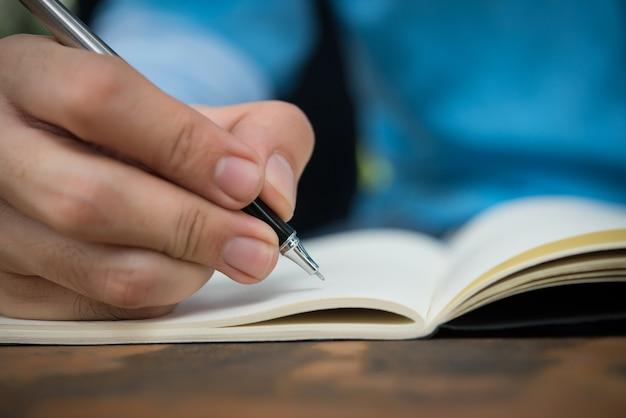 Mano del hombre escribe en el cuaderno. Foto gratis