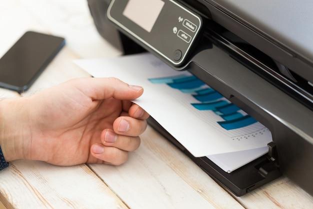 La mano del hombre haciendo copias. trabajando con impresora Foto Premium