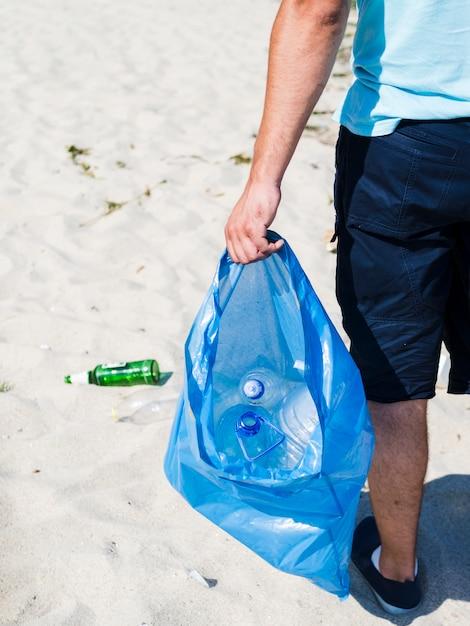 La mano del hombre llevando una bolsa de basura azul de plástico de desecho en la arena Foto gratis