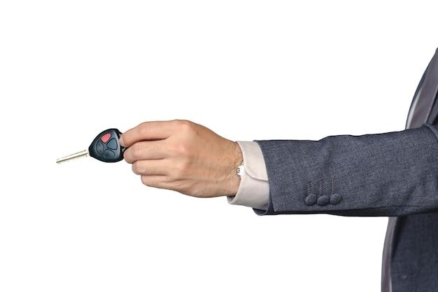 La mano de un hombre de negocios está enviando una llave del coche en su mano sobre un fondo blanco aislado. Foto Premium
